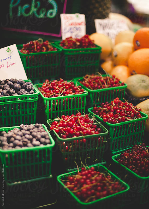 Pints of berries at the farmer's market. by Sarah Lalone for Stocksy United