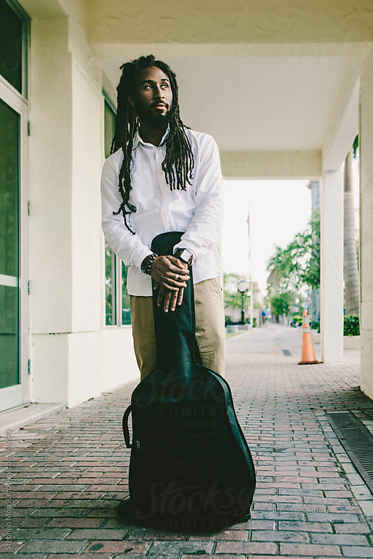 Young Man with Dreadlocks Holding Guitar Case by Stephen Morris for Stocksy United