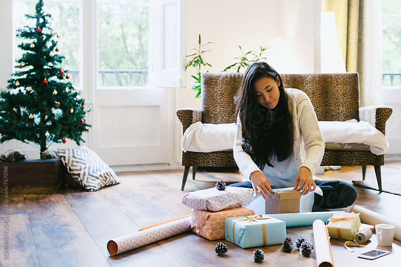 Asian woman wrapping Christmas gifts at home. by BONNINSTUDIO for Stocksy United