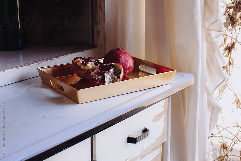 Pomegranates in White Kitchen by Gabrielle Lutze for Stocksy United