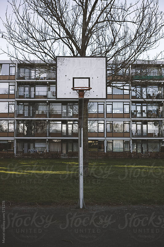 Basketball goal in front of an appartment block by Marcel for Stocksy United
