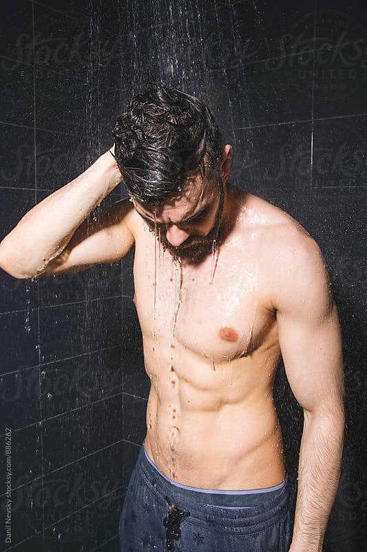 Man wearing pants having shower by Danil Nevsky for Stocksy United