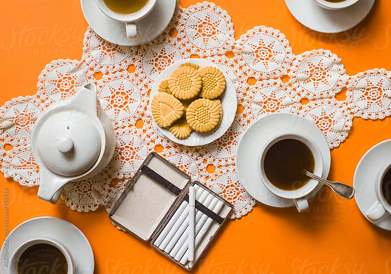Coffee cups with cookies on tablecloth on orange background / ook from above by Marko Milanovic for Stocksy United