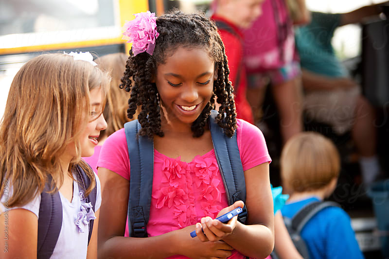 School Bus: Kids Use Cell Phone in Line by Sean Locke for Stocksy United
