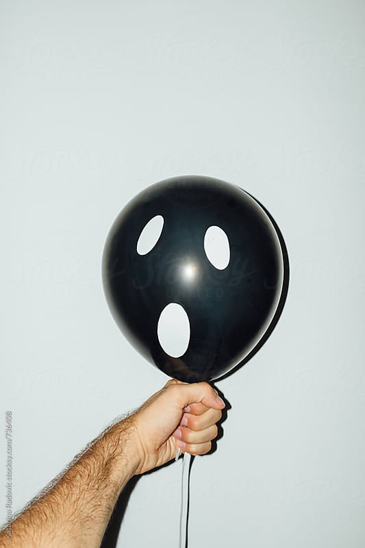 Man Holding Halloween Ghost Balloon by Katarina Radovic for Stocksy United