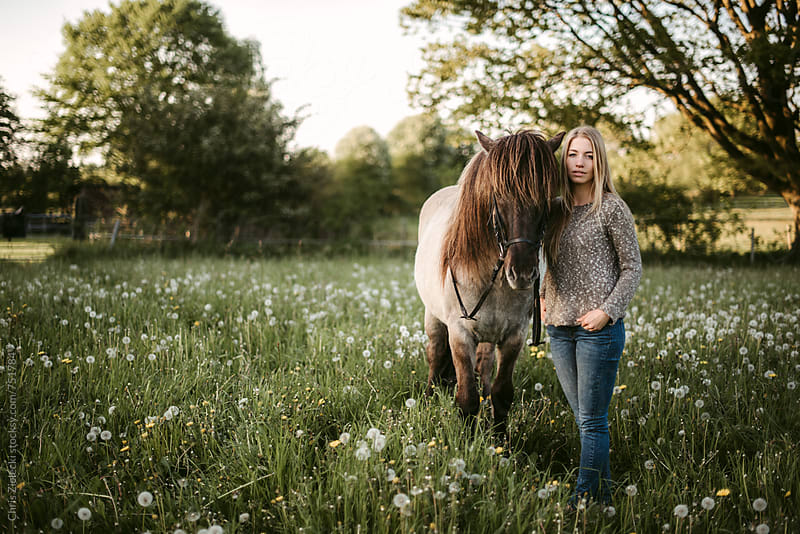 a girl standing by her horse on a meadow by Christian Zielecki for Stocksy United