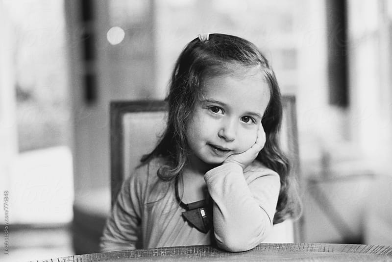 A cute young girl sitting at a kitchen table resting her head in her hand by Jakob for Stocksy United