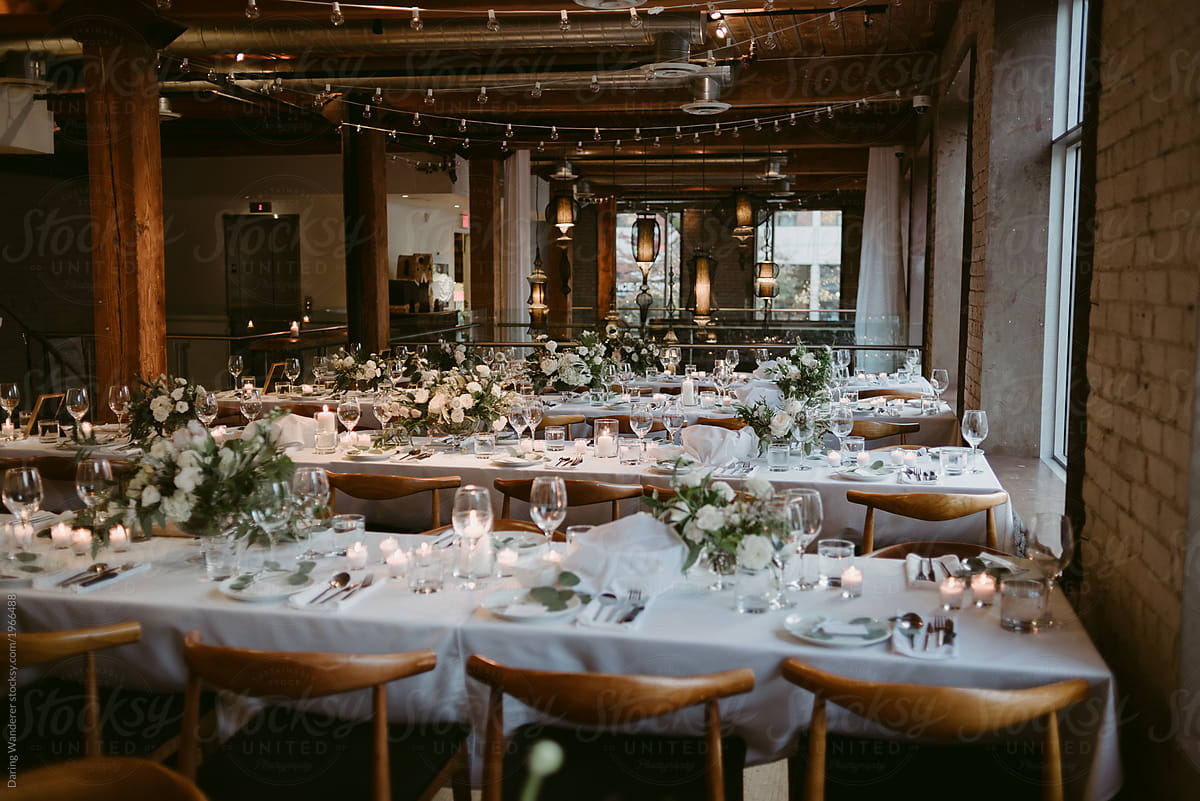 Long tables set up for wedding reception inside old building by Jess Craven  - Stocksy United