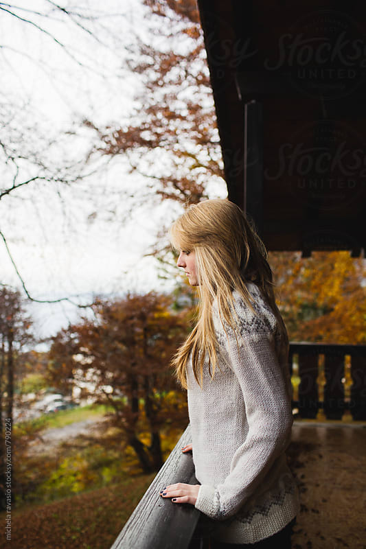 Girl looks the arrival of autumn from the balcony by michela ravasio for Stocksy United