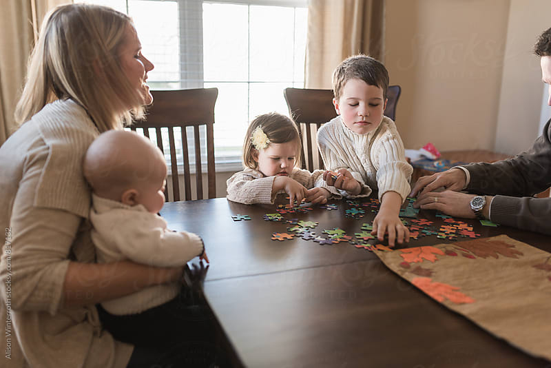 A Family Of 5 Puts Together A Puzzle by Alison Winterroth for Stocksy United