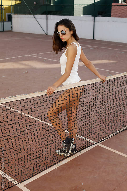 young woman at tenniscourt by Rene de Haan for Stocksy United