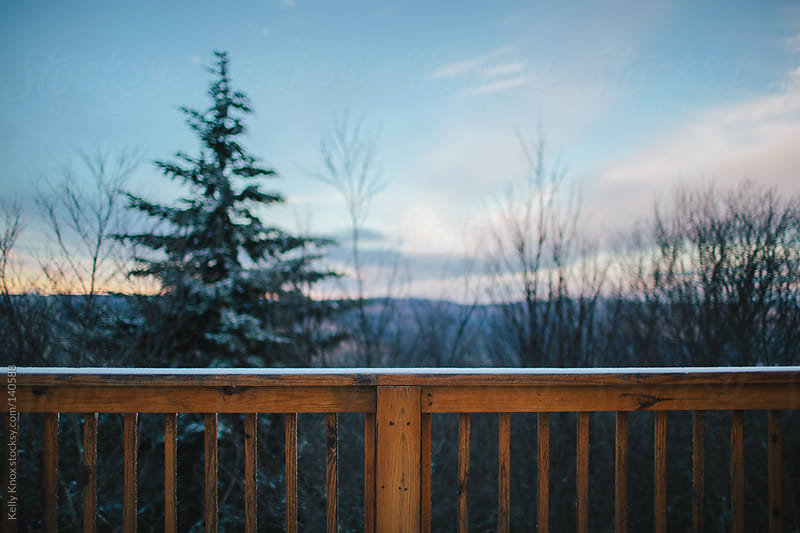 sunset view from the deck of a mountain cabin by Kelly Knox for Stocksy United
