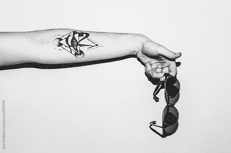 Persons with tattooed arm holding glasses by Igor Madjinca for Stocksy United