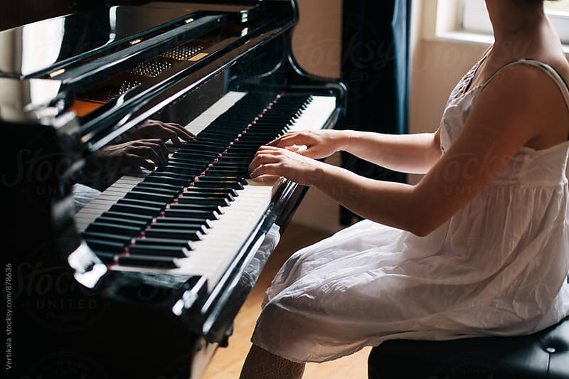 Woman in a white dress playing piano indoor by Marija Mandic for Stocksy United
