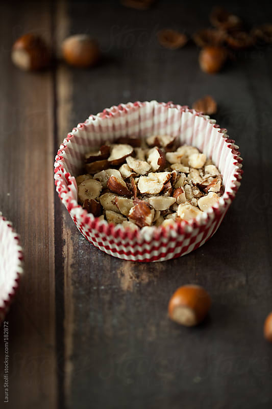 Chopped hazelnuts in cupcake liner by Laura Stolfi for Stocksy United