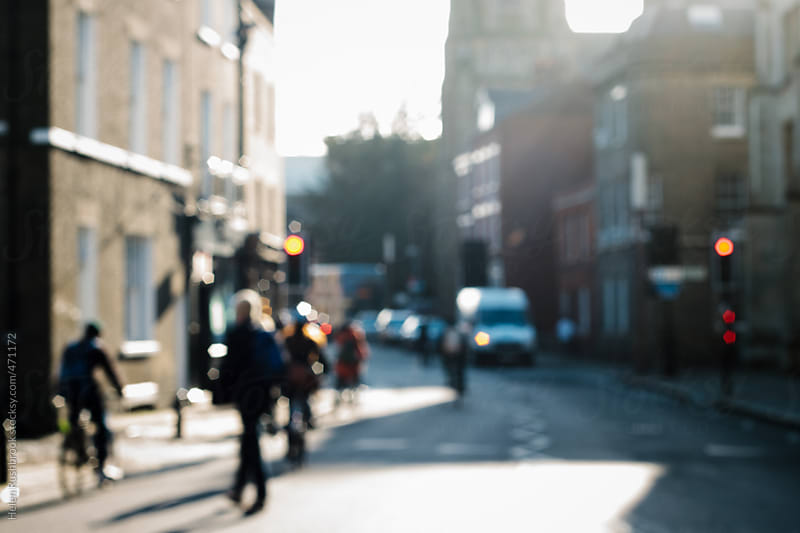 A blurred street scene, with pedestrians, cyclists and vehicles by Helen Rushbrook for Stocksy United