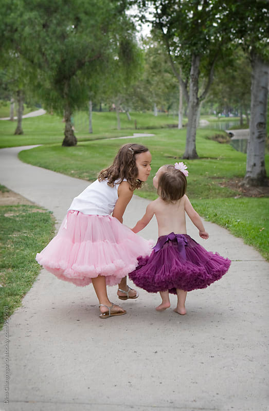 Two Sisters in Dresses Walking Down Path by Dina Giangregorio for Stocksy United