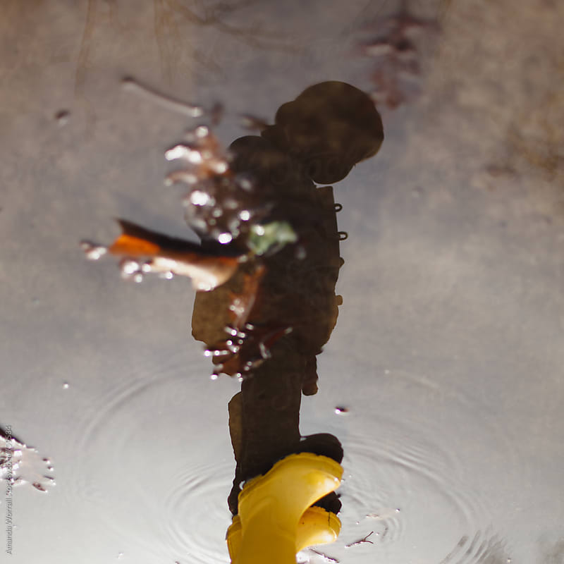 The reflection of a girl wearing yellow rain boots looking at herself in a puddle by Amanda Worrall for Stocksy United