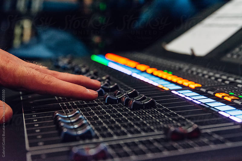 Sound engineer's hands on a mixer board faders by Gabriel (Gabi) Bucataru for Stocksy United