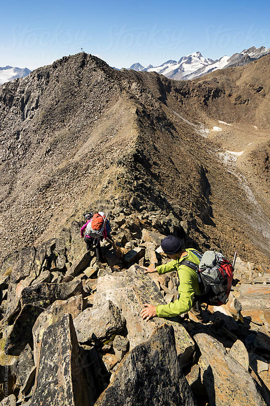 2 climbers traversing a ridge by Tristan Kwant for Stocksy United