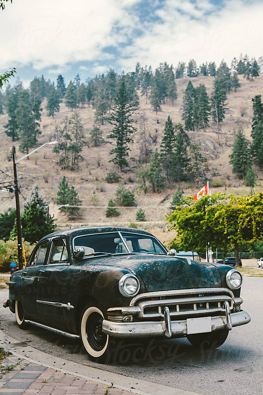 Old car in the street with mountains behind by kkgas for Stocksy United