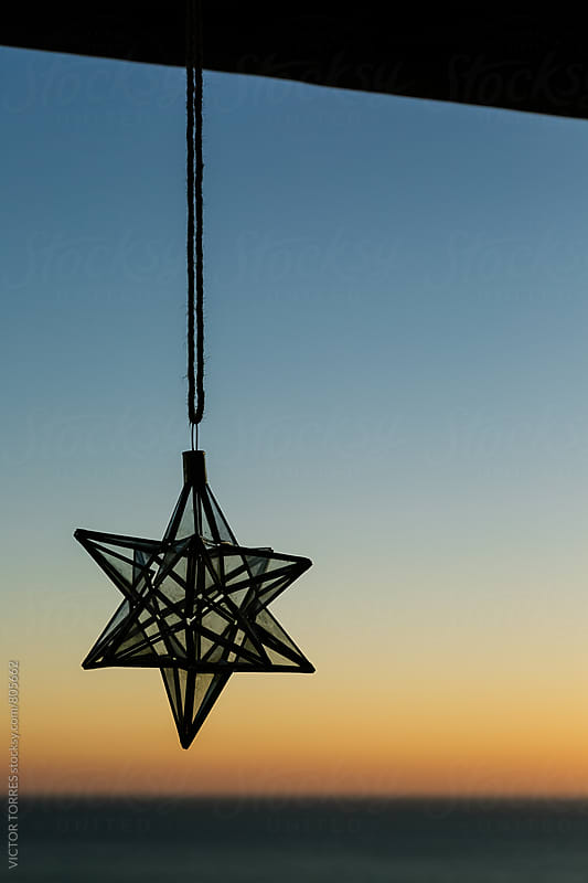 Christmas Star Hanging with a Beautiful Sunset Behind by VICTOR TORRES for Stocksy United