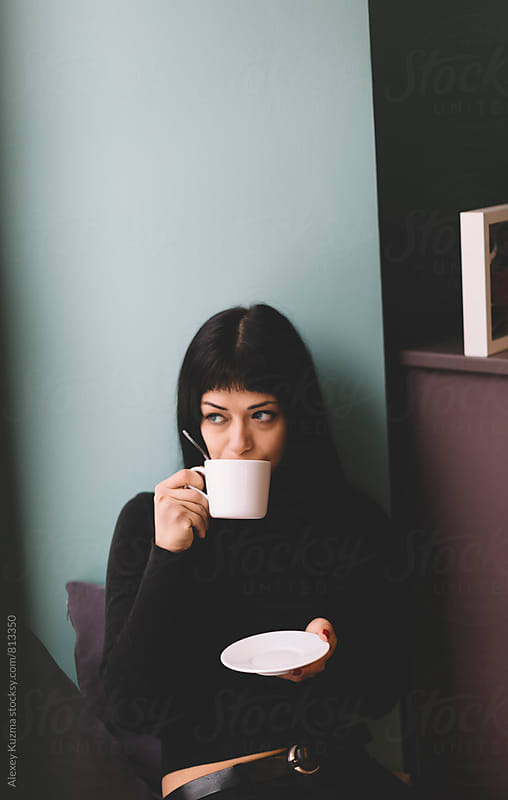 portrait of real young woman sitting in a Coffee Shop. by Alexey Kuzma for Stocksy United