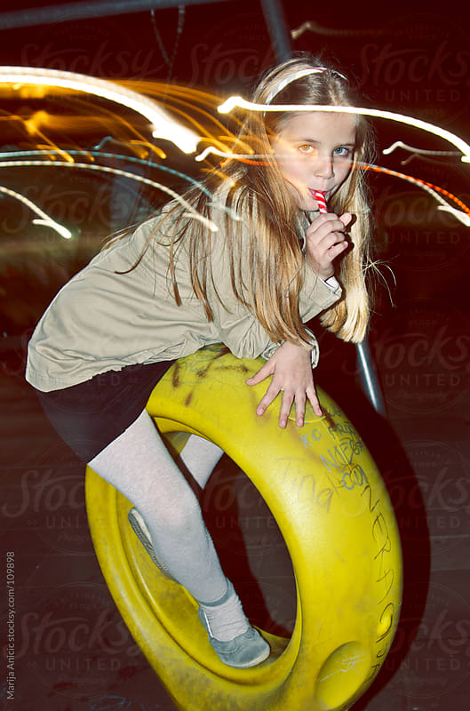 Seven year blonde girl with lollipop on playground by Marija Anicic for Stocksy United