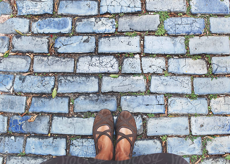 woman standing on a blue cobblestone street by Kelly Knox for Stocksy United