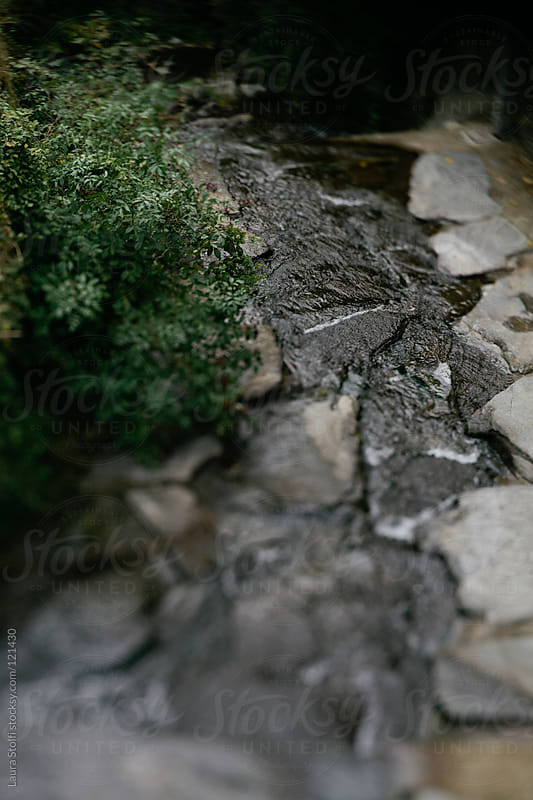 Mountain stream flowing amongst stones  by Laura Stolfi for Stocksy United