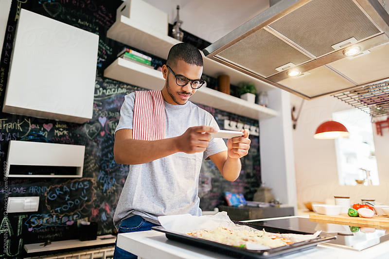 Man taking a photo with his phone to the handmade pizza at home. by BONNINSTUDIO for Stocksy United