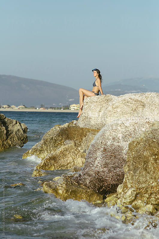 Woman sitting on the rock by the sea by Brkati Krokodil for Stocksy United