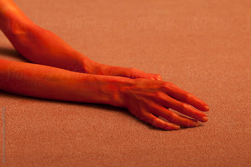 red painted hand of a young lady on floor by Ulaş and Merve for Stocksy United