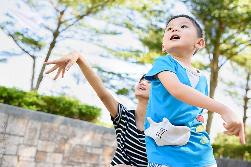 Kid and mother playing paper airplane in sunlight by Lawren Lu for Stocksy United
