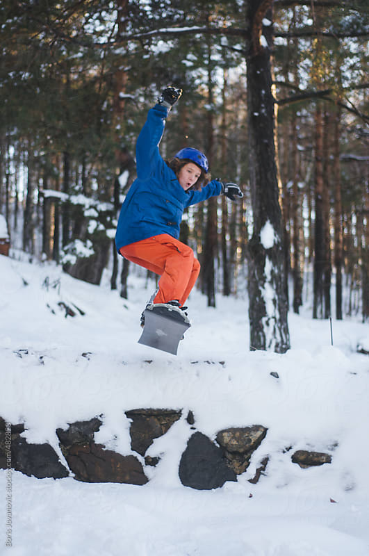 Young boy snowboarding by Boris Jovanovic for Stocksy United