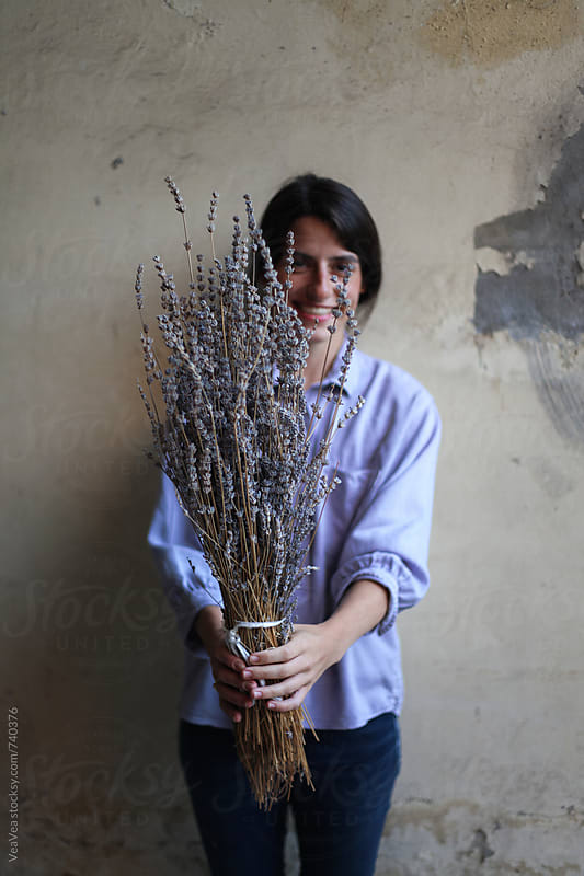 Happy woman holding a bouquet of lavender flowers in front of her by Marija Mandic for Stocksy United