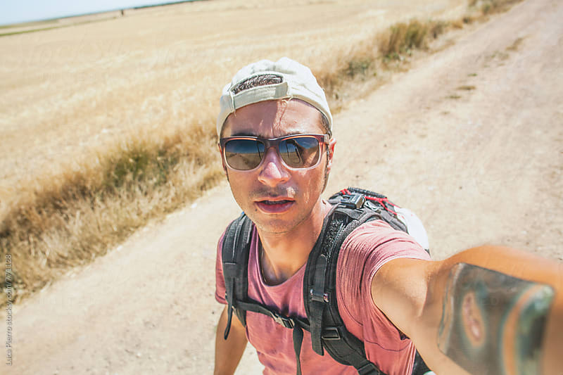 Tired hiker taking a selfie  by Luca Pierro for Stocksy United