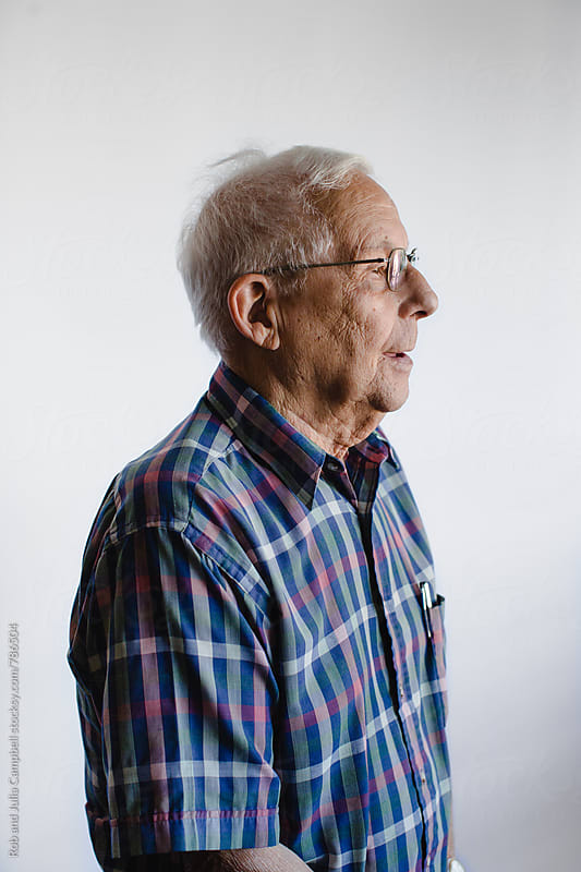 Profile of senior man on white background by Rob and Julia Campbell for Stocksy United