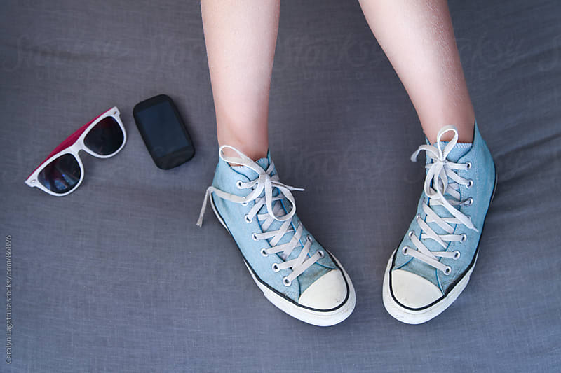 Girl hanging out with her sneakers, glasses and electronic device by Carolyn Lagattuta for Stocksy United