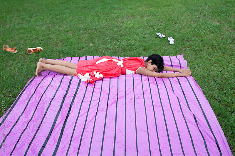 Teenage girl lying on the ground and relaxing by PARTHA PAL for Stocksy United