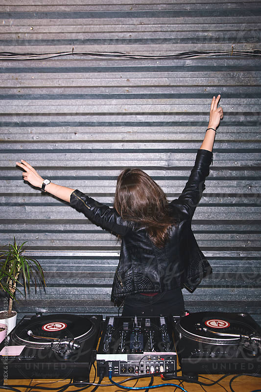 Female DJ having fun holding hands up with peace signs by Danil Nevsky for Stocksy United