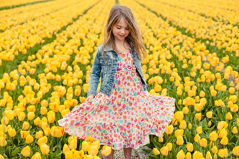 Little girl in a flower dress standing in a yellow tulip field by Cindy Prins for Stocksy United