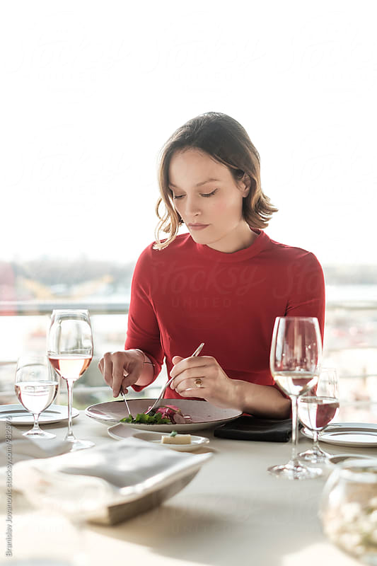 Beautiful Woman in the Red Dress Sitting at the Table Having Lunch at the Restaurant by Branislav Jovanović for Stocksy United