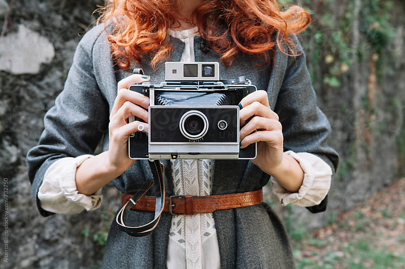 Woman with red hair and vintage camera by Alberto Bogo for Stocksy United