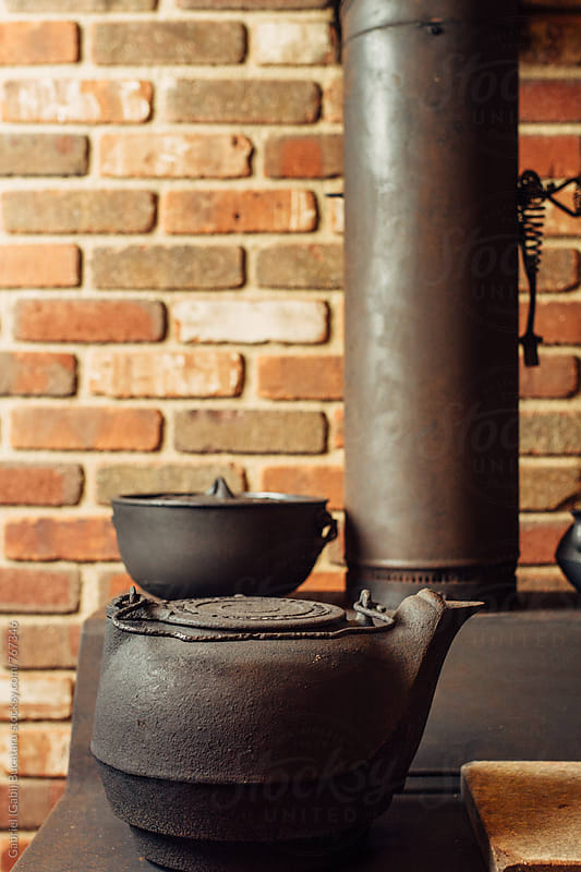 Old wood stove and cast iron kettle by Gabriel (Gabi) Bucataru for Stocksy United
