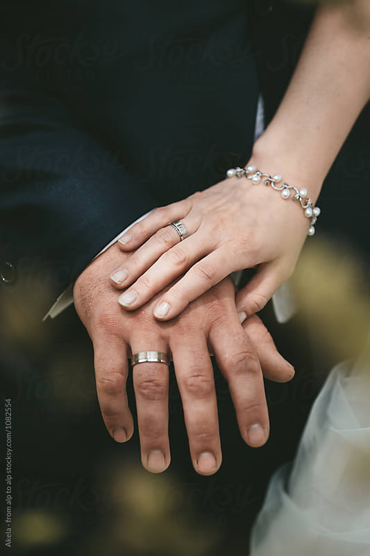 bride is holding her grooms hand tender with wedding rings by Leander Nardin for Stocksy United