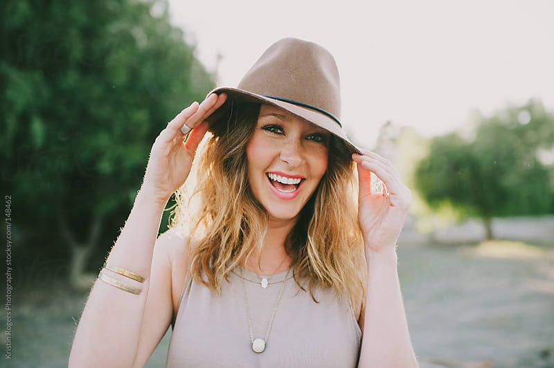 Pretty woman playing with hat and laughing by Kristin Rogers Photography for Stocksy United