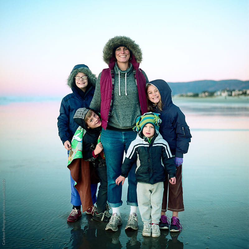 Mom and four kids at the beach in winter by Carleton Photography for Stocksy United