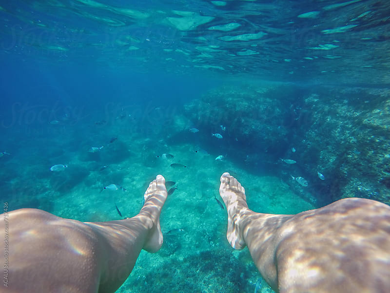 Woman legs in transparent sea water by ACALU Studio for Stocksy United