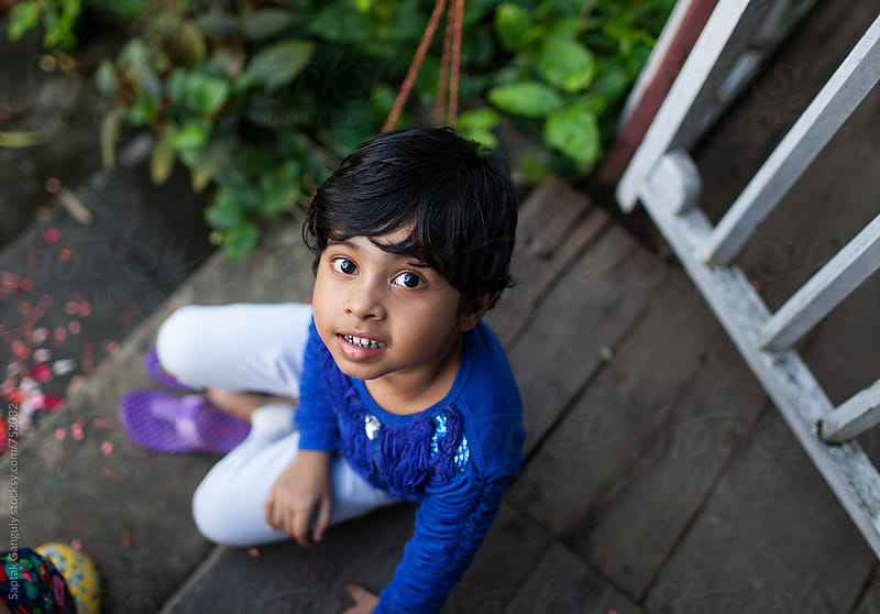 Top view of a child sitting on a porch and looking up with a smile by Saptak Ganguly for Stocksy United